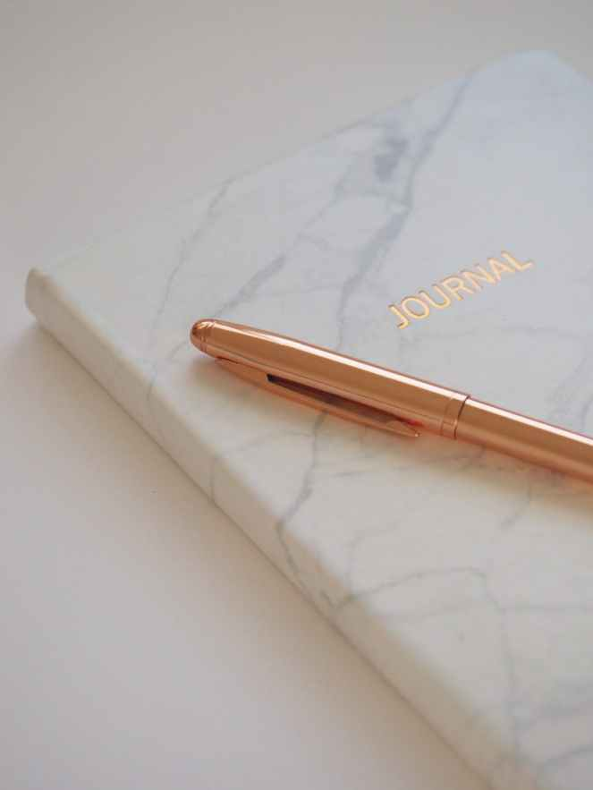 gold pen on journal book